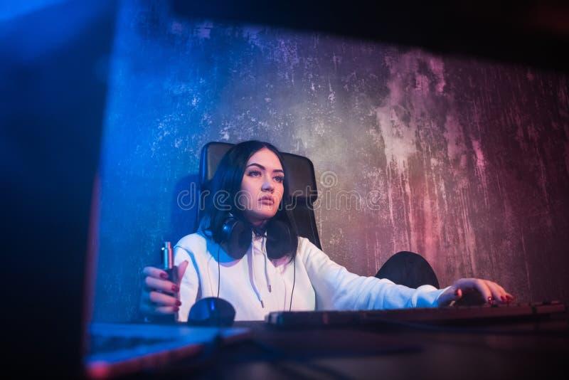 Стекла и hoodie молодой тазобедренной женщины брюнет нося, сидя вниз столом с компьютером пока курящ e-сигарету стоковая фотография rf