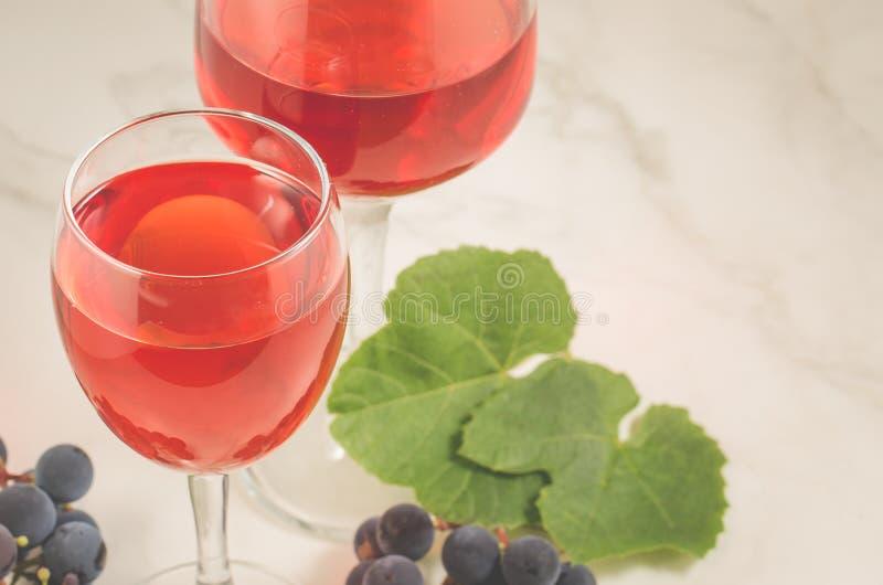 Стекла красного вина и виноградины/стекел красного вина и виноградина на белой таблице Селективный фокус стоковое изображение rf