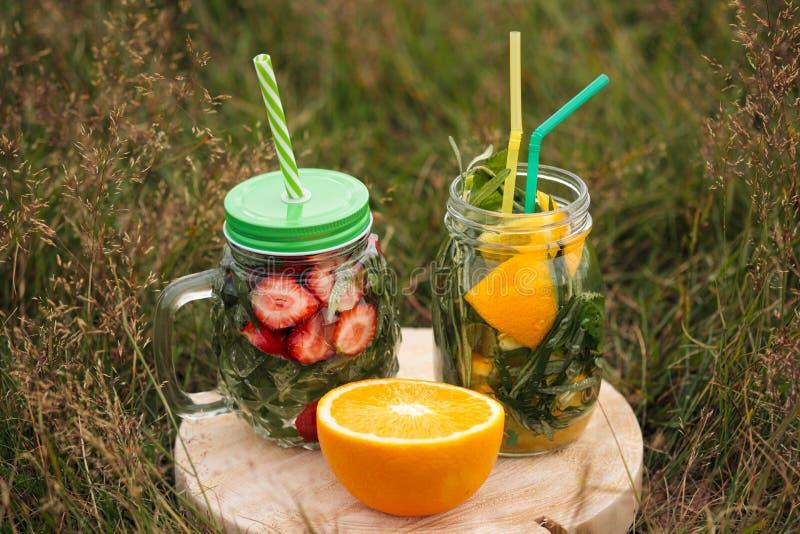 2 стекла лимонада с tubules стоят на деревянной доске на зеленой траве Напитки лета от клубник и стоковое изображение