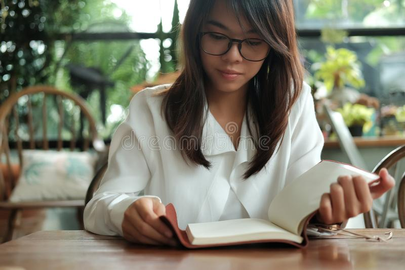 Стекла молодой женщины студента нося сидя на библиотеке и readi стоковое изображение rf