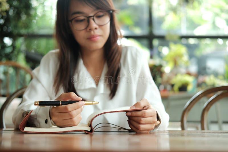 Стекла молодой женщины студента нося сидя на удерживании библиотеки p стоковая фотография rf