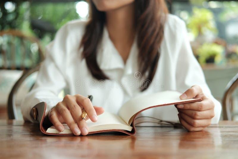 Стекла молодой женщины студента нося сидя на удерживании библиотеки p стоковые изображения rf