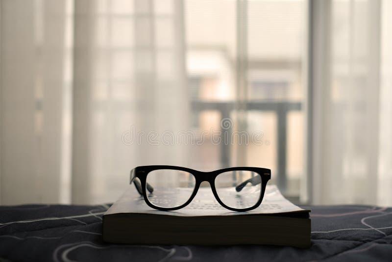 Стекла на книге в комнате кровати с окном занавесов стоковая фотография