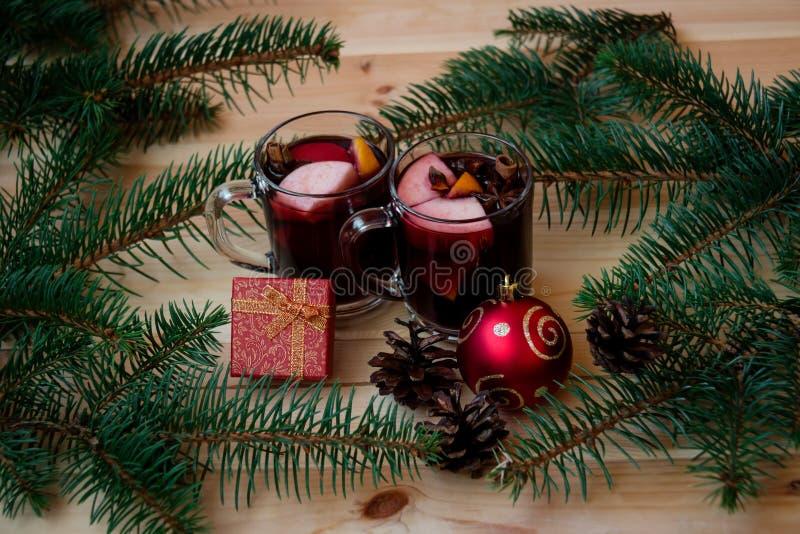 Стекла обдумыванного вина с шариком ветвей, подарочной коробки и рождества ели стоковое фото