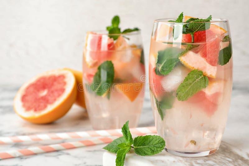 Стекла освежающего напитка с грейпфрутом и мятой на мраморной таблице стоковое фото rf