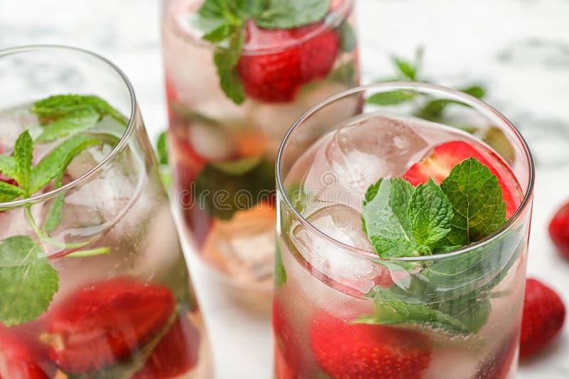 Стекла освежающего напитка с клубникой и мятой на таблице стоковая фотография