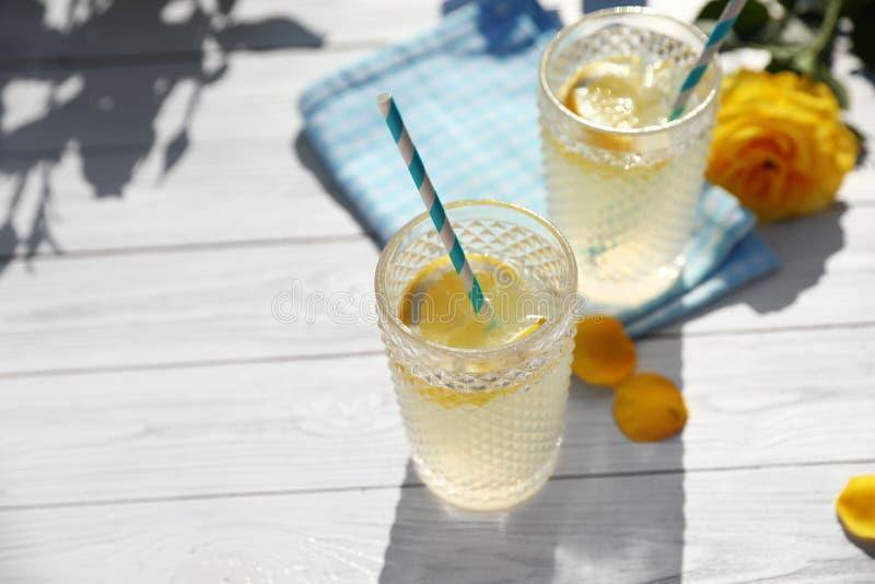 Стекла освежая лимонада и красивого желтого цвета подняли на белый деревянный стол стоковые фотографии rf