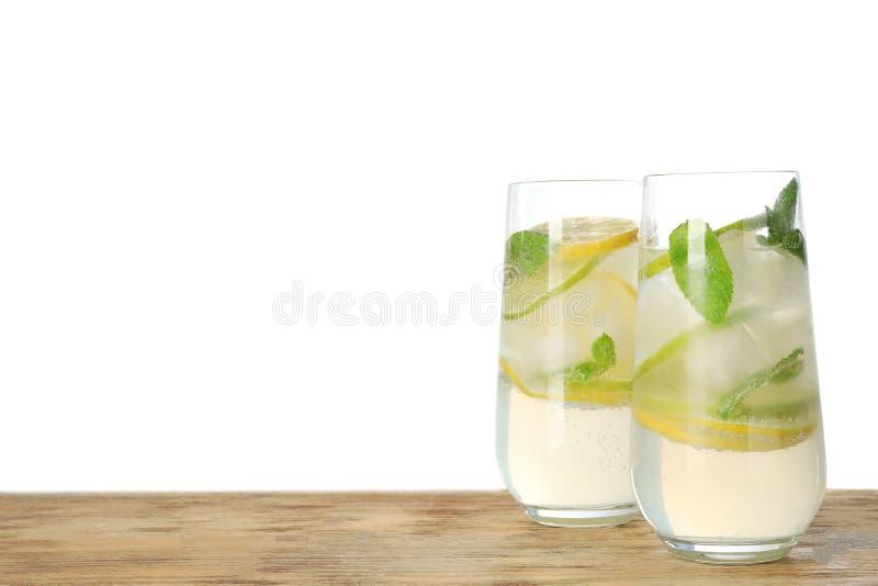 Стекла освежая лимонада на деревянном столе против белой предпосылки стоковые фото