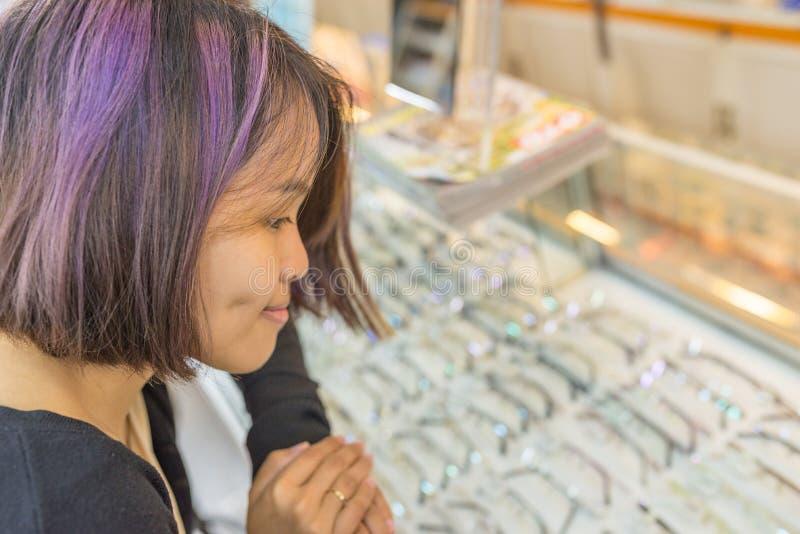 Стекла покупки маленькой девочки в магазине optician стоковое изображение