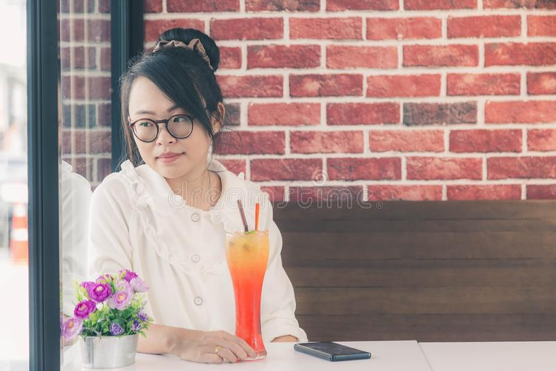 Стекла прекрасной азиатской женщины нося сидя на кофейне стоковое изображение