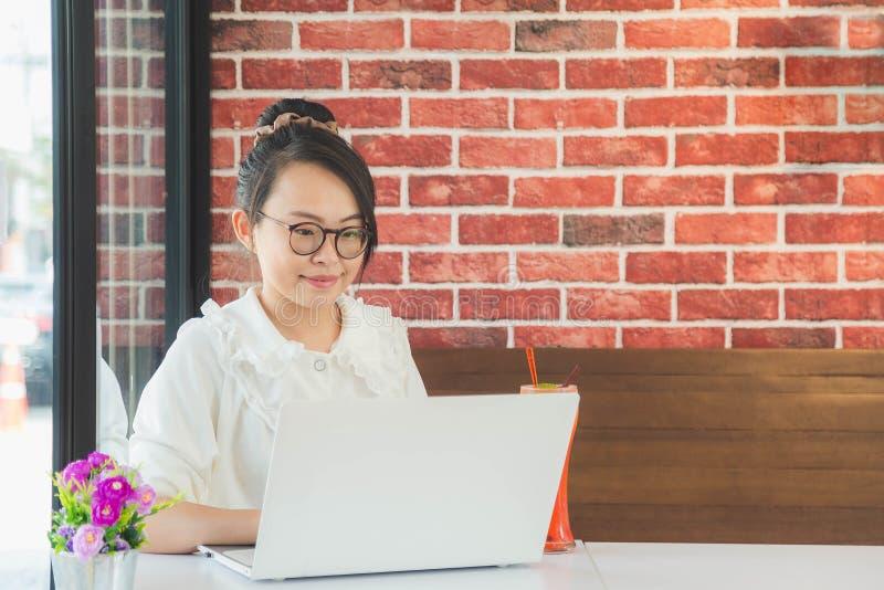 Стекла прекрасной азиатской женщины нося сидя на кофейне с ноутбуком стоковая фотография rf
