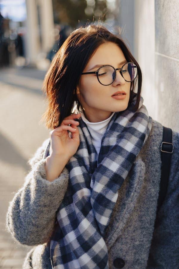 Стекла привлекательной маленькой девочки нося в пальто идя на солнечный день стоковые изображения rf