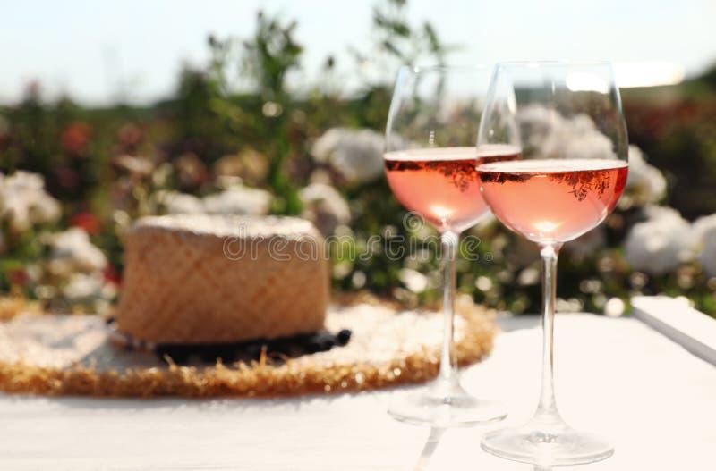 Стекла розового вина и соломенной шляпы на белом деревянном столе outdoors стоковое фото rf