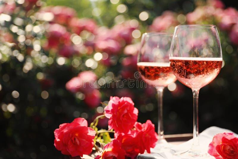 Стекла розового вина на таблице в зацветая саде стоковое изображение rf