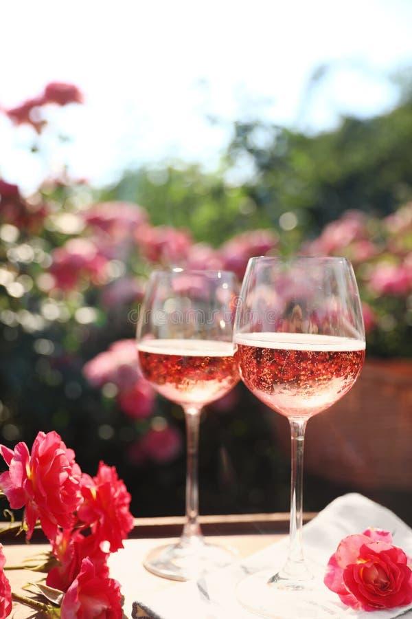 Стекла розового вина на таблице в саде стоковое фото rf