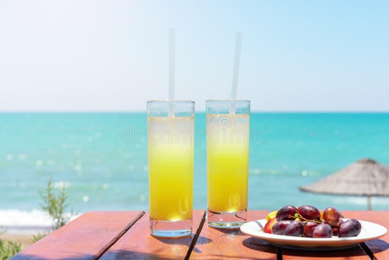 2 стекла свежего тропического фруктового сока на пляже, и плита с виноградинами и арбузом на таблице, против моря Holi стоковое изображение