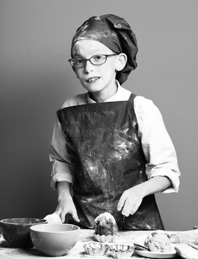 Стекла стоя близко таблица с прессформами, красочными bawls и брызгают шоколадный торт с напудренным сахаром на красной студии стоковое изображение