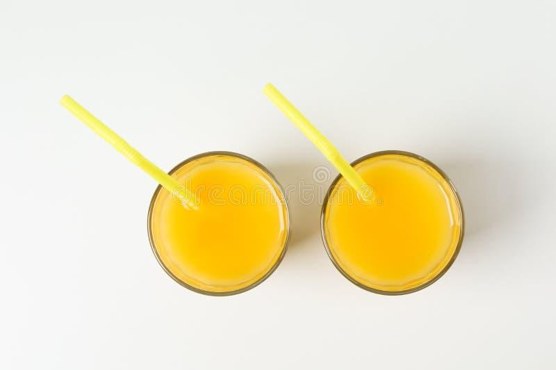 Стекла с апельсиновыми соками и tubules на белых предпосылке, взгляде сверху и космосе для текста стоковые изображения rf