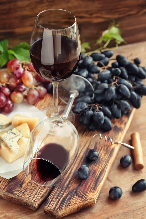 Стекла с вином, свежими виноградинами и сыром на деревянной доске стоковое изображение