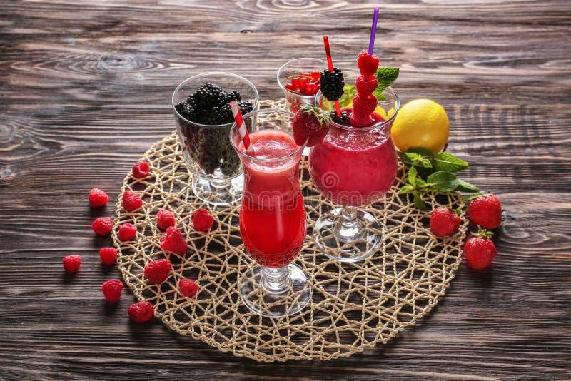 Стекла с вкусными smoothies ягоды на деревянном столе стоковое фото