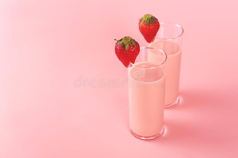 2 стекла с молоком клубники на розовой предпосылке стоковая фотография
