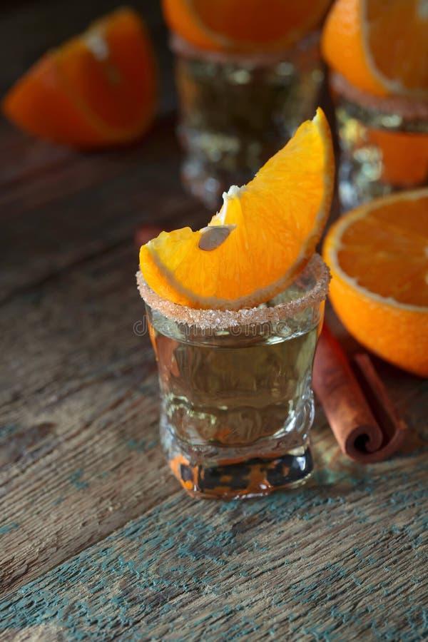 Стекла текила, оранжевых кусков и ручек циннамона стоковое изображение