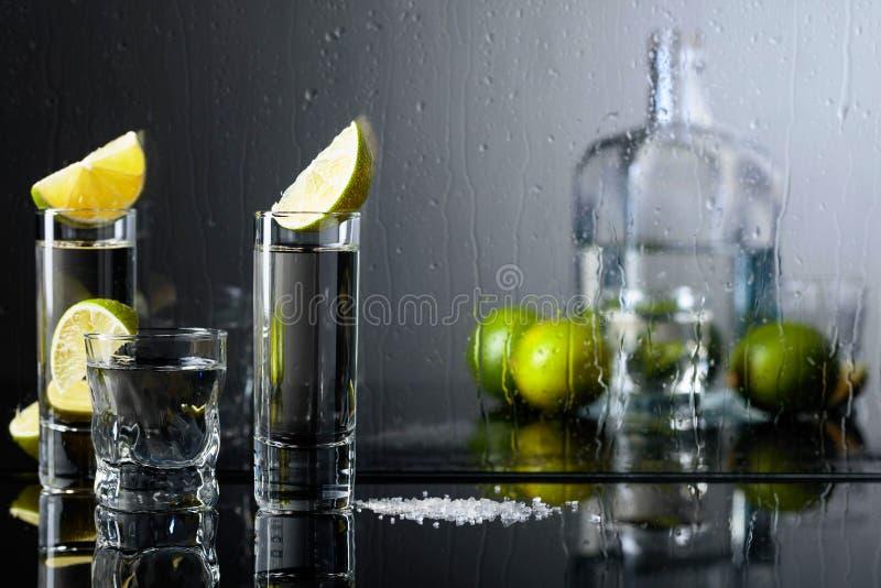 Стекла текила с известкой и солью на черной отражательной предпосылке стоковая фотография