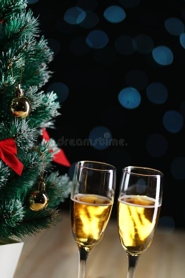 2 стекла Шампани около зарева l малой рождественской елки темного стоковая фотография rf