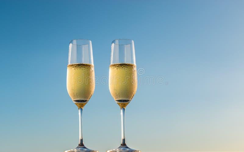 Стекла шампанского изолированные на предпосылке голубого неба стоковое фото