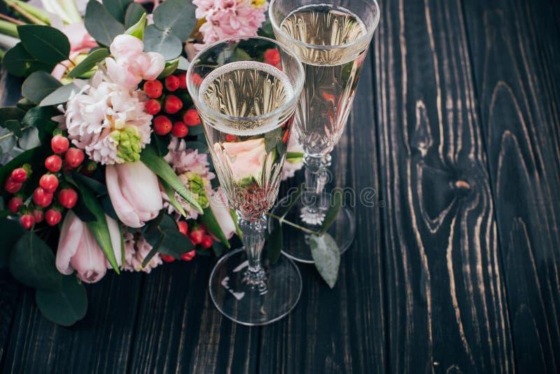 2 стекла шампанского и букет розовых цветков на темноте сватают стоковая фотография rf