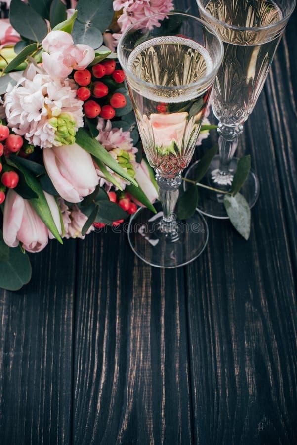 2 стекла шампанского и букет розовых цветков на темноте сватают стоковое изображение
