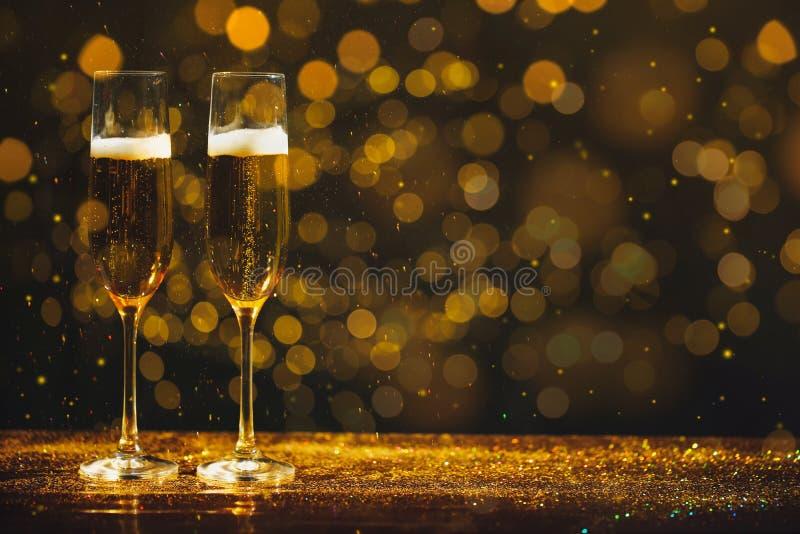 Стекла шампанского и золотого яркого блеска на таблице против запачканной предпосылки стоковые фотографии rf