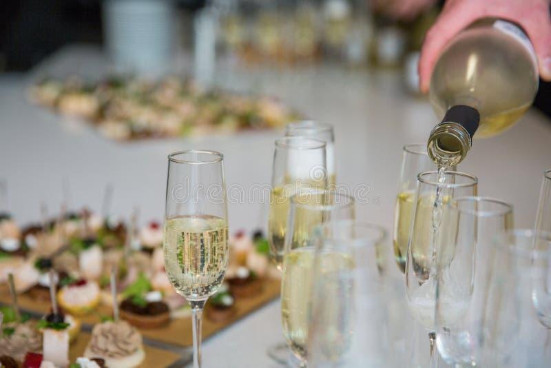 Стекла Шампань на таблице белизна торжества изолированная принципиальной схемой Партия спирта и коктеиля стоковое изображение rf