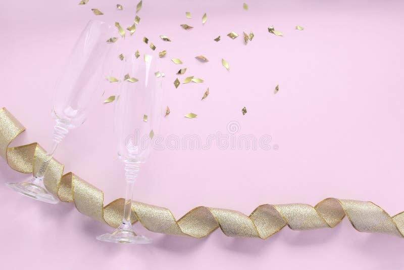 Стекла Шампань с золотыми сусалью и лентой confetti на розовой предпосылке Отпразднуйте концепцию партии, минимальный стиль r стоковые фотографии rf