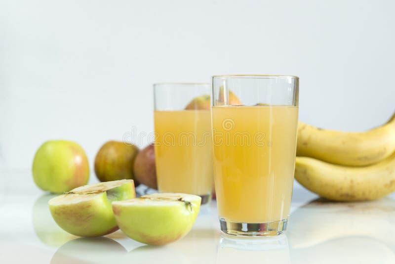 2 стекла яблочного сока, сока в стеклах, свежих яблоках на a стоковое фото