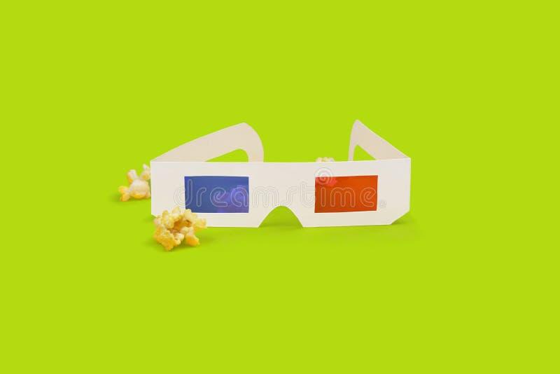стекла 3d с попкорном на зеленой предпосылке стоковое фото