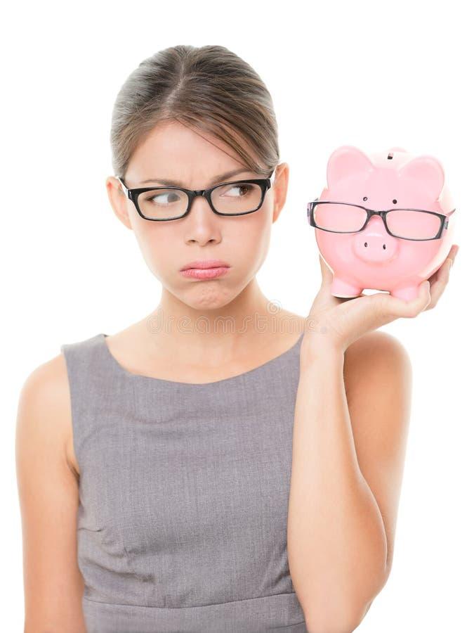 Стекла Upset женщины нося держа piggy банк стоковая фотография
