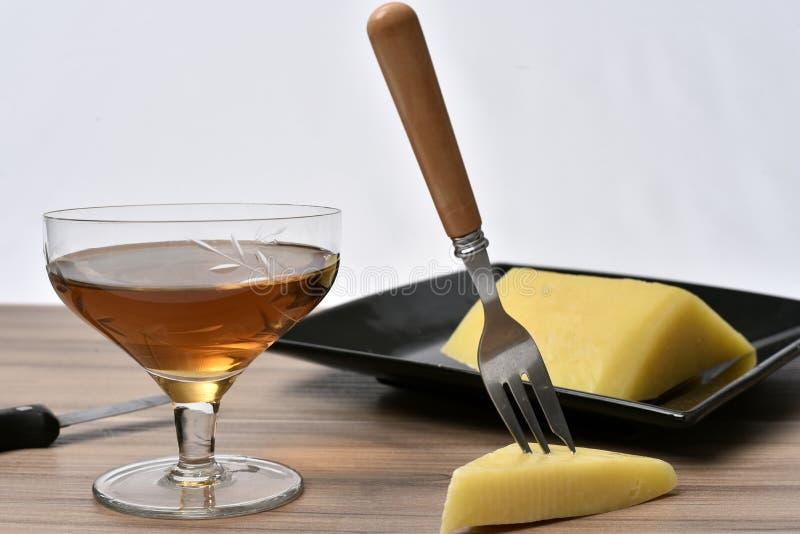 Стекло алкогольного напитка с сыром на таблице на белой предпосылке стоковая фотография