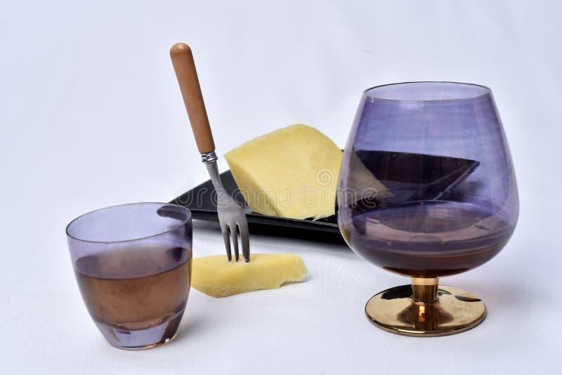 Стекло алкогольного напитка с сыром на таблице на белой предпосылке стоковое изображение