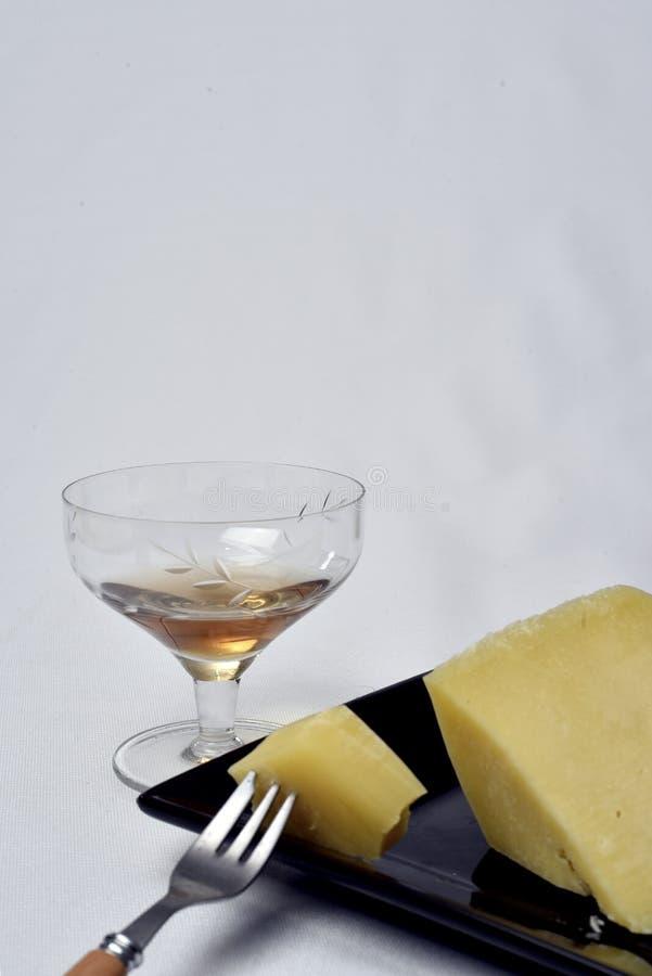 Стекло алкогольного напитка с сыром на таблице на белой предпосылке стоковое фото