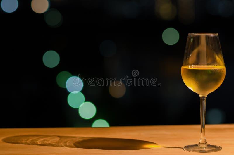 Стекло белого вина и своей тени на деревянном столе бара крыши с красочным bokeh света и космоса города для текста стоковое фото rf