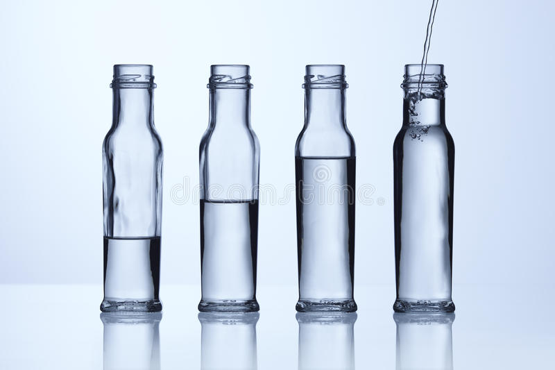 стекло бутылки различное выравнивает воду стоковые изображения rf