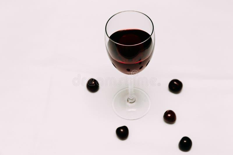 Стекло вина вишни на красных и белых ягодах предпосылки и вишни стоковая фотография rf