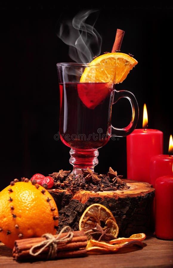 Стекло вина рождества горячего обдумыванного на деревянном столе с видом, апельсинами и красными свечами против черной предпосылк стоковое фото rf