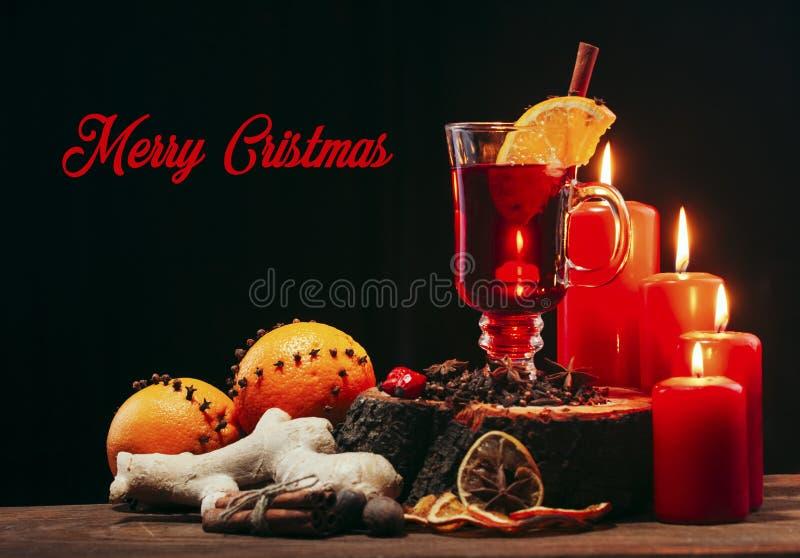 Стекло вина рождества горячего обдумыванного на деревянном столе с видом, апельсинами и красными свечами против черной предпосылк стоковая фотография rf