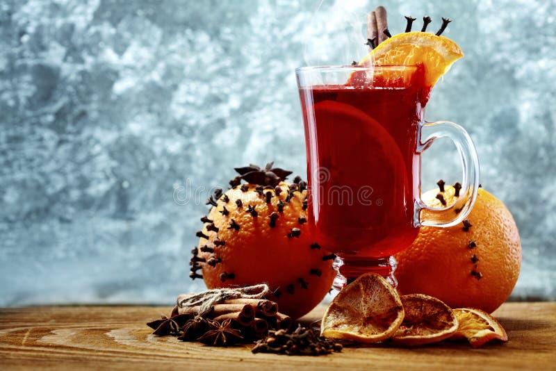 Стекло вина рождества горячего обдумыванного на деревянном столе с видом и апельсинами против замороженного окна скопируйте космо стоковые изображения rf