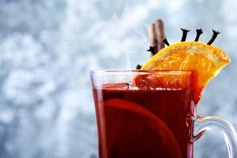 Стекло вина рождества горячего обдумыванного на деревянном столе с видом и апельсинами против замороженного окна closeup скопируй стоковое изображение