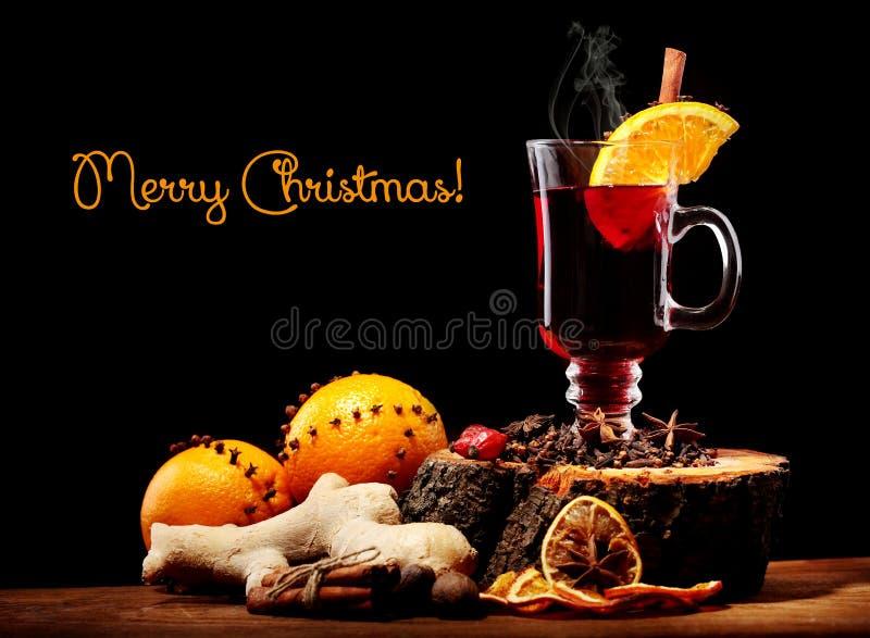 Стекло вина рождества горячего обдумыванного с видом и апельсинами на деревянном столе против черной предпосылки С надписью весел стоковое изображение