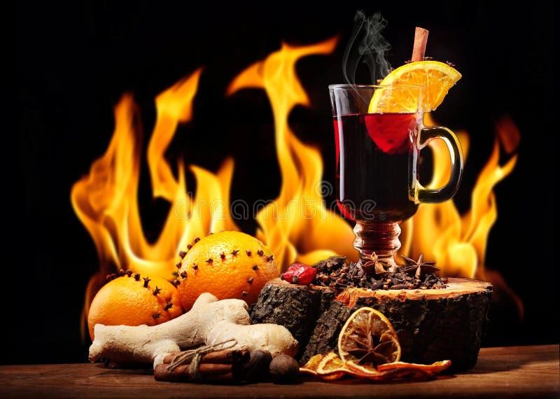 Стекло вина рождества горячего обдумыванного с видом и апельсинами на деревянном столе против камина карточка 2007 приветствуя сч стоковая фотография rf