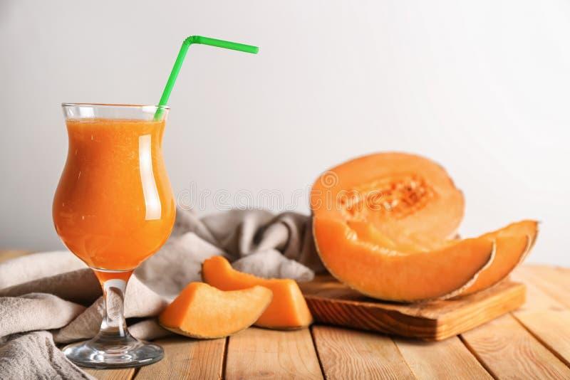 Стекло вкусного smoothie дыни на деревянном столе стоковое фото